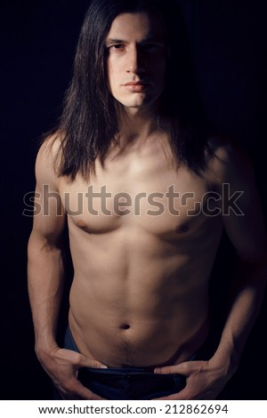 handsome young man with long hair naked torso on black background