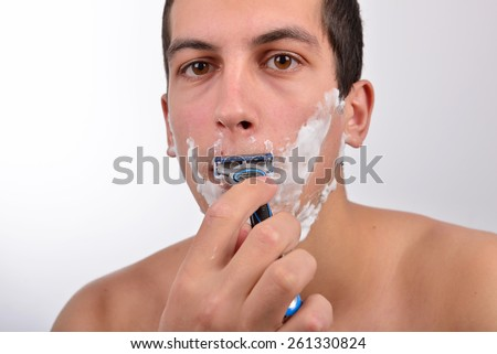 Handsome young man with lots of shaving cream on his face is shaving with razor - stock photo