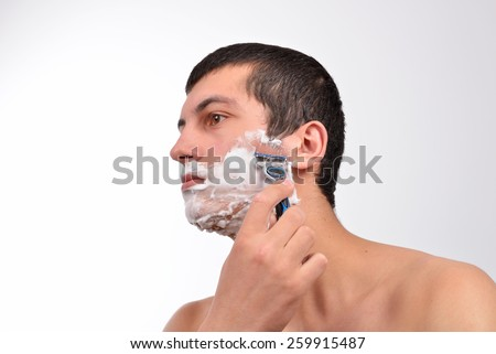 Handsome young man with lots of shaving cream on his face preparing to shave with razor