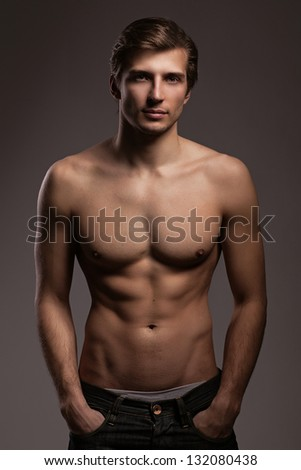 Handsome young man with naked torso on a grey background - stock photo