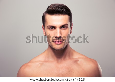Handsome young man with nude torso looking at camera over gray background - stock photo