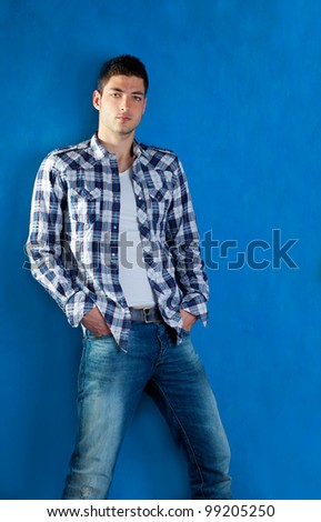 handsome young man with plaid shirt denim jeans in blue background - stock photo