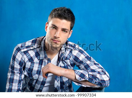 handsome young man with plaid shirt on blue background - stock photo