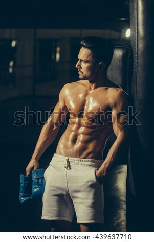 Handsome young man with sexy muscular body bare torso and chest holding boxing gloves - stock photo