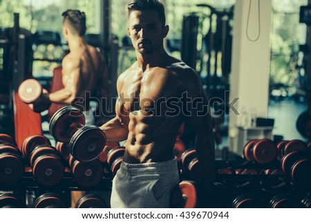 Handsome young man with sexy muscular wet body bare torso and chest training with heavy dumbbell in gym