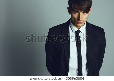 Handsome young man with short hair wearing classic black&white suit and tie posing over gray background. Classic style. Studio shot - stock photo