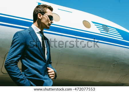 Handsome young man with short hair wearing classic blue suit and black tie posing over airplane. Classic style. Outdoor shot