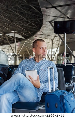 handsome young man with short hair working on the tablet, sitting on a chair with things at the airport waiting for his flight - stock photo