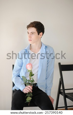 Handsome young man with single pink rose - stock photo