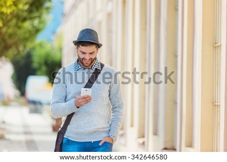 Handsome young man with smartphone outside in the town - stock photo