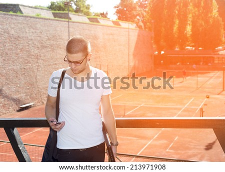 Handsome young man with sunglasses looks at smart phone - stock photo