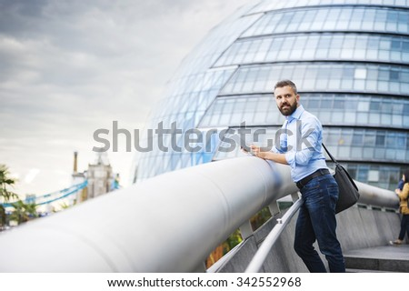 Handsome young man with tablet in the streets of London - stock photo