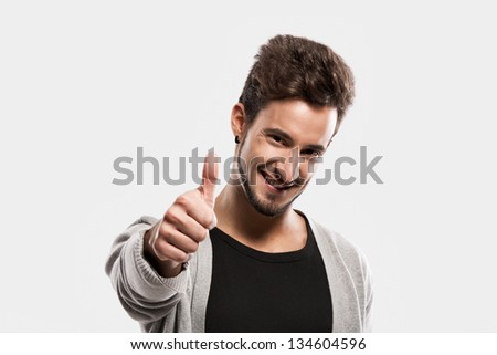 Handsome young man with thumbs up, over a gray background