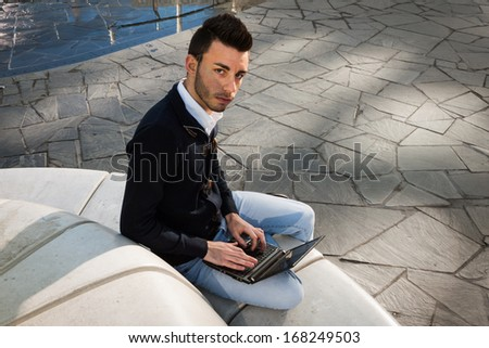 Handsome young man working at computer outdoor