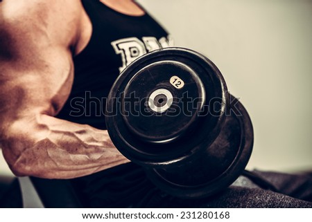 Handsome young man working out with dumbbells in fitness -  power training