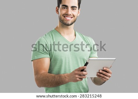 Handsome young man working with a tablet, isolated over gray background - stock photo