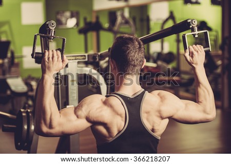 Handsome young man workout in fitness gym - strong mans bodybuilders back