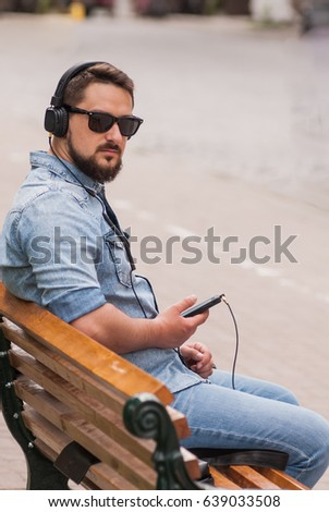 handsome young man write sms and hear music