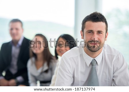 Handsome young manager posing with colleagues in background - stock photo