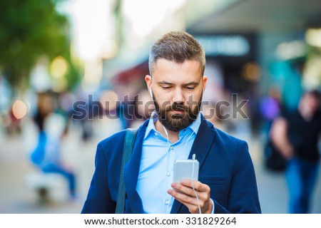 Handsome young manager with smartphone in London - stock photo
