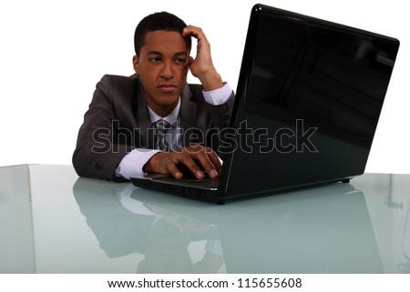 handsome young manager working on laptop - stock photo