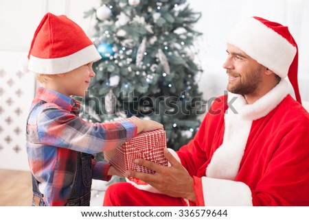 Handsome young men in costume of Santa Claus is sitting in chair near Christmas tree. He is giving a box of gift to his son. They are smiling - stock photo