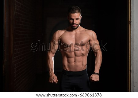 Handsome Young Model Standing Strong in the Fitness Center and Flexing Muscles - Muscular Athletic Bodybuilder Man Posing After Exercises
