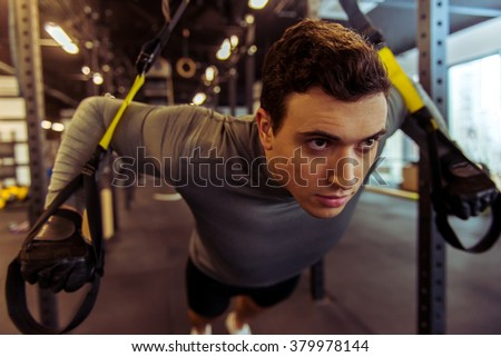 Handsome young muscled man training with trx while working out in gym - stock photo