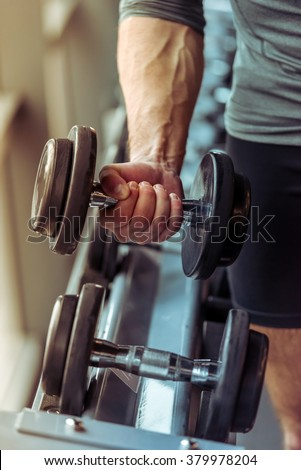 Handsome young muscled man working out with dumbbells in gym, close-up - stock photo