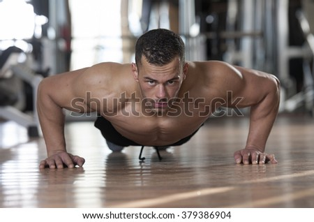 handsome young muscular man in a fitness gym