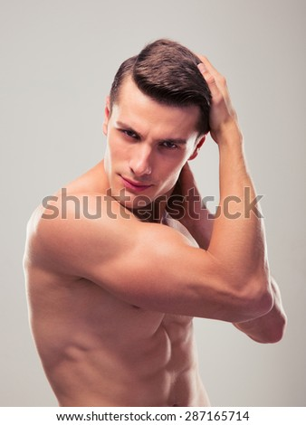 Handsome young muscular man posing over gray background - stock photo