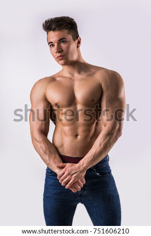 Handsome young muscular man shirtless wearing jeans, on light background in studio shot