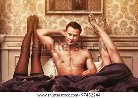 handsome young muscular man with two women in bedroom - stock photo