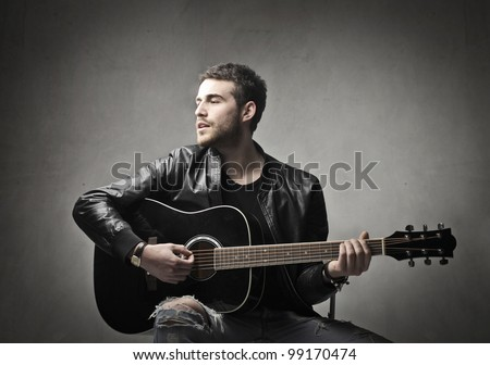Handsome young musician playing the guitar and singing - stock photo