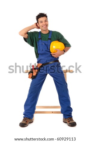 Handsome young Nepalese carpenter wearing a blue overall, tool-belt and helmet, resting on the workbench. Studio shot. White background. - stock photo