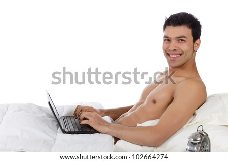Handsome young nepalese man in bed with laptop,  against white sheets. Studio shot. White background - stock photo