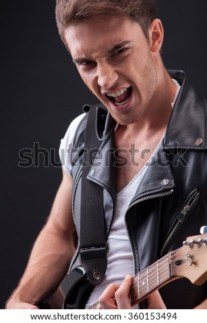 Handsome young performer is making great music - stock photo