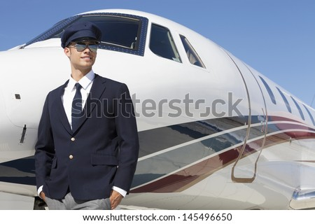 Handsome young pilot standing by private airplane - stock photo