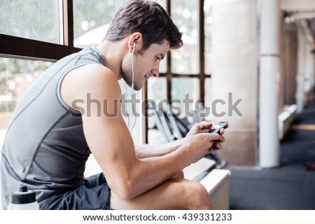 Handsome young portsman listening to music and using his cellphone sitting on windowcill at the gym