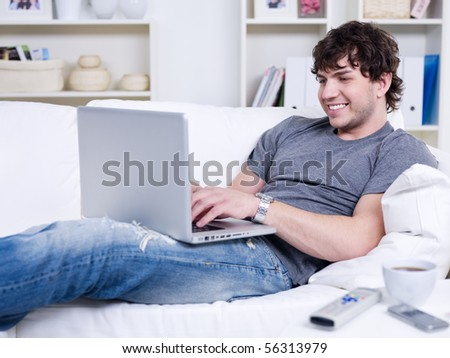 Handsome young relaxing man using laptop and lying on the sofa
