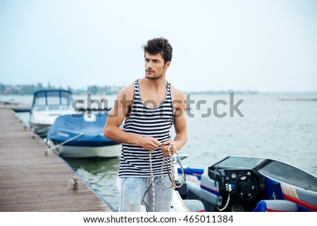Handsome young sailor holding rope at the pier and looking away