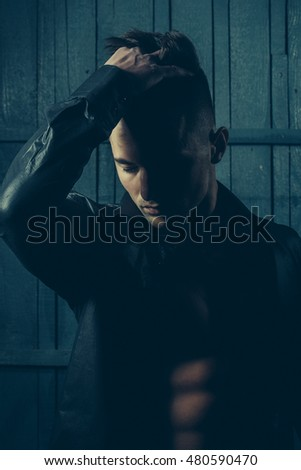 Handsome young sexy man with beautiful muscular chest in shirt in studio on wooden background
