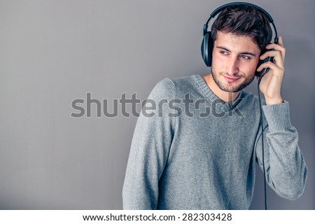 Handsome young smiling man listening to music in front of a grey wall - stock photo