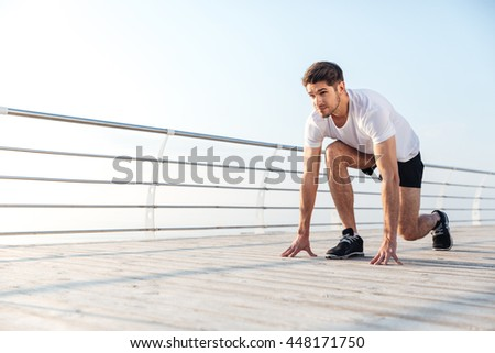 Handsome young sportsman preparing for start running in the morning at sunrise - stock photo