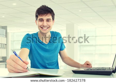 handsome young student happy about research results from the internet