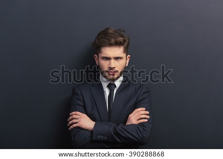 Handsome young student in classic suit is looking at camera, standing with crossed arms against blackboard