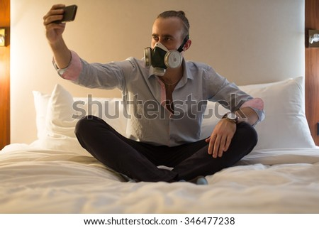 Handsome young stylish caucasian man in respirator sitting on the bed in the bedroom, doing selfie