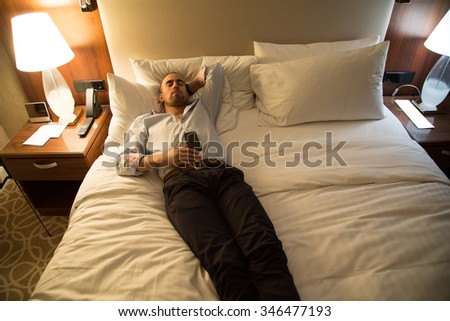 Handsome young stylish caucasian man sleeping on the bed in the bedroom