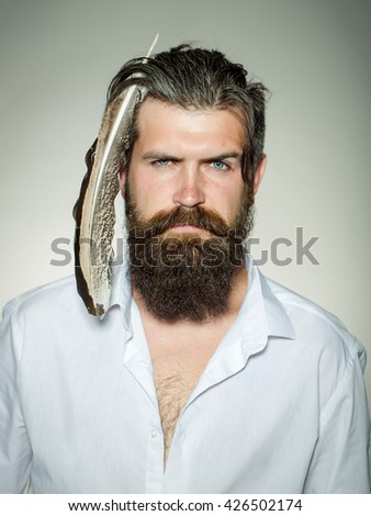 Handsome young stylish hipster man with long beard and big feather in hair in white shirt standing in studio on grey background