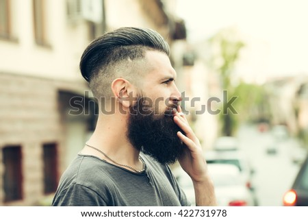 Handsome young stylish hipster man with long beard in grey shirt standing outdoor smoking cigarette